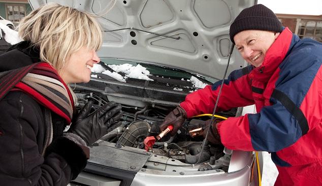 Ein älterer Mann in einer roten Jacke gibt einer blonden Frau Starthilfe, beide stehen vor dem geöffneten Motorraum des betreffenden Autos