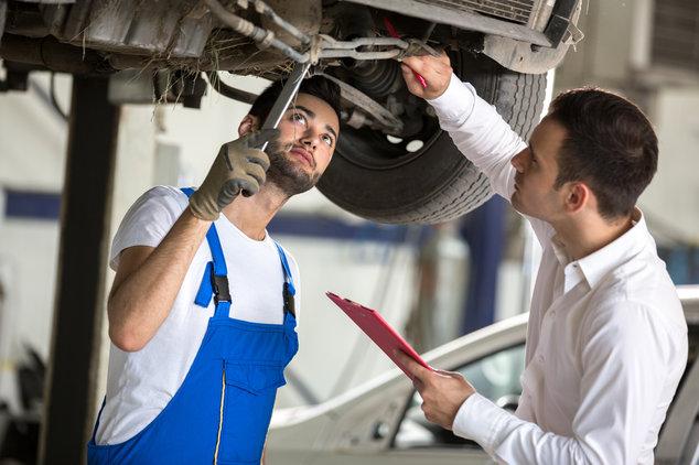 Unterseite Auto mit Mechaniker in Werkstatt