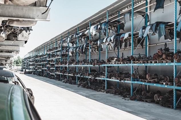 Hunderte verschiedene Autoteile lagern hängend oder liegend in hohen Regalen auf einem Recyclinghof