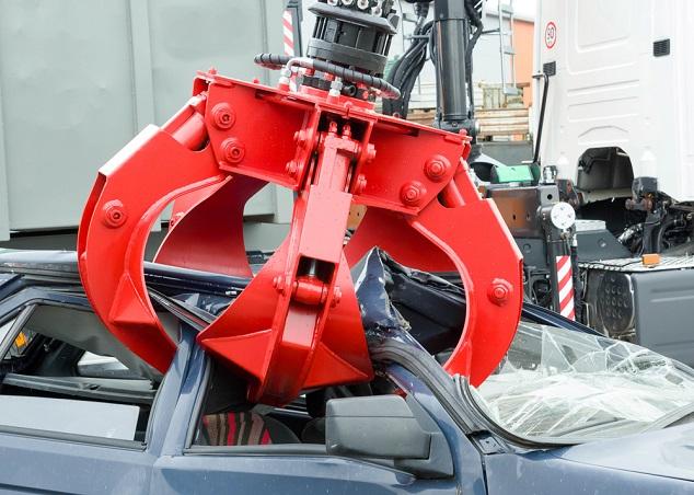Rote Schrottplatzkralle greift ein kaputtes Auto bei der Autoentsorgung