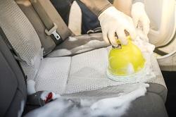 Autositze werden mit Polsterreinigungsgerät und schäumenden Pflegemitteln gereinigt