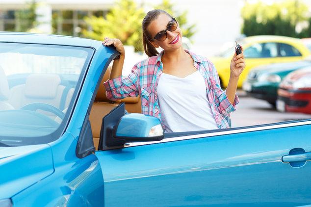 Junge Frau neben Cabrio mit Autoschlüssel