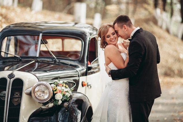Brautpaar neben Hochzeitsauto