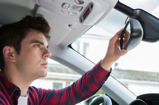 Mann stellt Rückspiegel im Auto ein