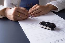 Vertragsunterzeichnung mit Autoschlüssel auf dem Vertrag
