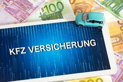 """Ein türkisfarbenes Modellauto und ein Tablet-PC mit dem Schriftzug """"KFZ-Versicherung"""" liegen auf ausgebreiteten Euro-Geldscheinen"""