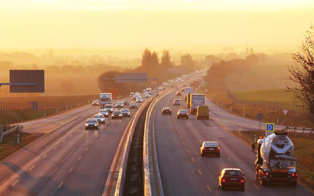 Der Verkehr fließt auf einer sechsspurigen Autobahn bei aufgehender Sonne und Nebel
