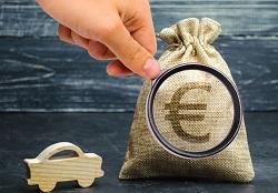 Ein kleines Holzauto steht neben einem Jutesack mit Eurozeichen, das von einer mit der Hand gehaltenen Lupe vergrößert wird