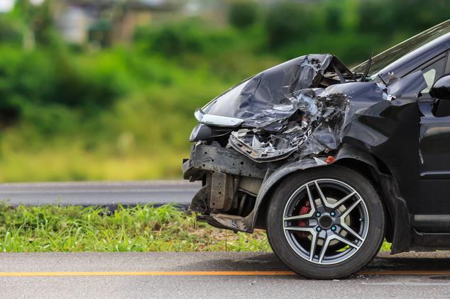 Ein an der vorderen linken Seite stark beschädigtes schwarzes Auto steht seitlich im Bild