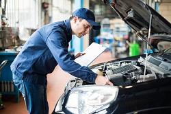 Mechaniker überprüft Motor in der Werkstatt