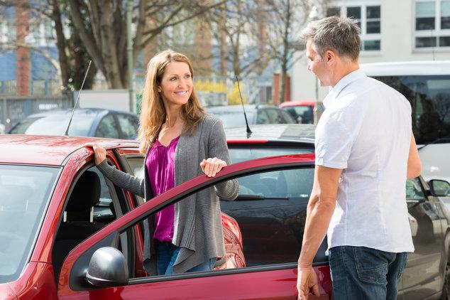 Frau steigt zur Probefahrt ins Auto