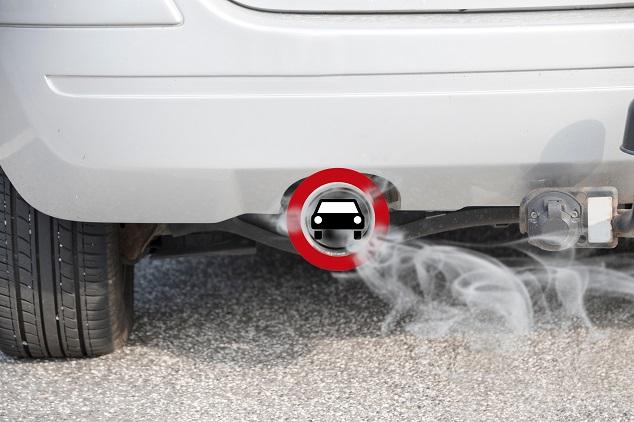 Nahaufnahme eines Auspuffs, aus dem Abgase entweichen, während vor dem Auspuff ein Verbotsschild montiert ist