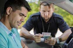 Seitenaufnahme von einem Mann im Auto, der von einem Polizisten kontrolliert wird. Der Polizist streckt den Kopf durchs Seitenfenster und hält die Papiere in der Hand.