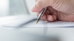 Detailaufnahme einer Hand, die einen Kugelschreiber zum Ausfüllen eines Formulars hält